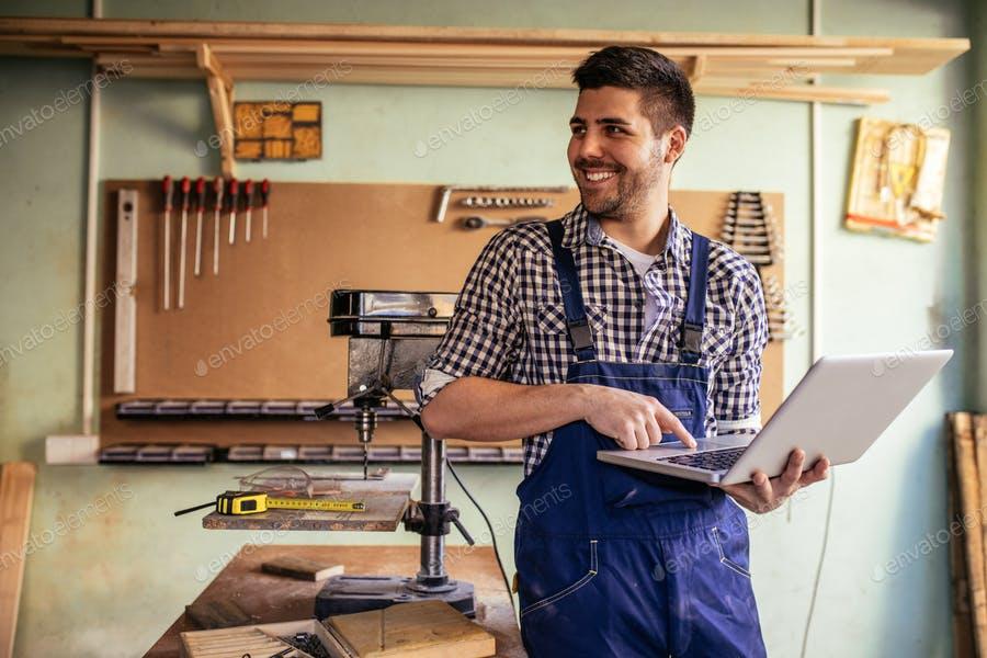 عکس نجار در حال کار با لپ تاپ در کارگاه