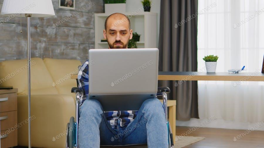 عکس مرد در حال کار با لپ تاپ روی ویلچر